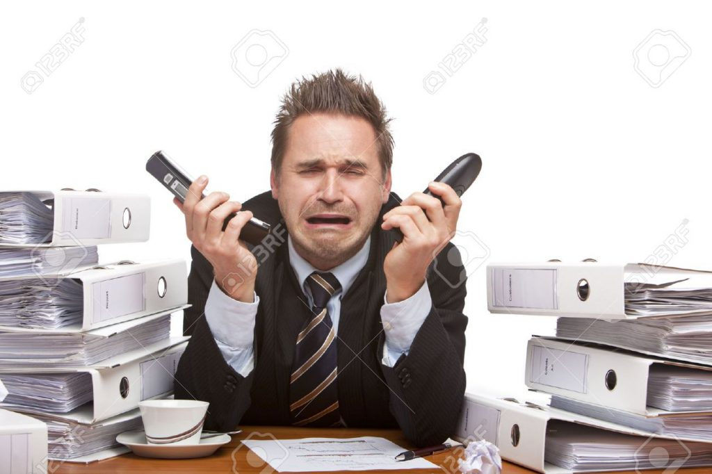 6057445-Young-businessman-is-sitting-on-desk-holding-two-telephones-and-crying-because-of-unmanageable-work--Stock-Photo