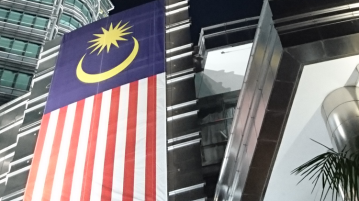 Malaysian flag hanging off of Kuala Lumpur's Petronas Twin Towers.