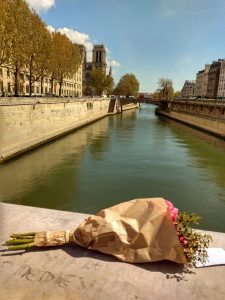 Flowers are left on a bridge with the Cathedral in the background