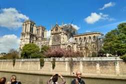 Parisians and tourists look upon the fire-damaged Notre Dame cathedral from the banks of the Seine.