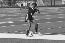 Greyscale photo of Black girl practising football