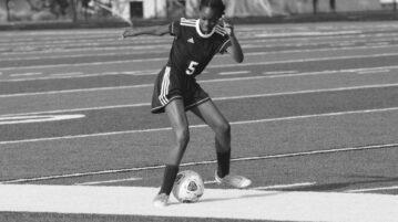 Greyscale photo of Black girl practising football